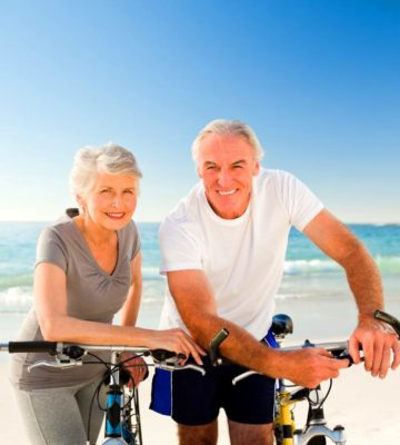 older couple on beach with bikes